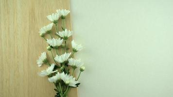 witte bloemen plat lag op houten plaat en grijze witte achtergrond foto