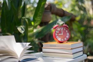 rode wekker met boek over de tuinachtergrond van de huisaard