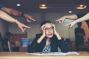 gefrustreerde zakenvrouw zittend aan de tafel in kantoor foto