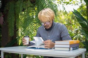 jonge hipster baard man koffie drinken tijdens het lezen van boeken in eigen tuin met de natuur