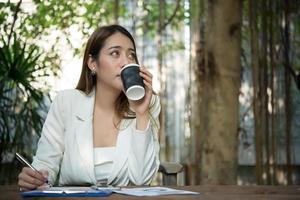 jonge zakenvrouw zitten in een kantoor een kopje koffie drinken