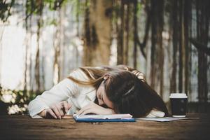 moe en uitgeput freelance vrouw slapen op laptopcomputer in kantoor foto