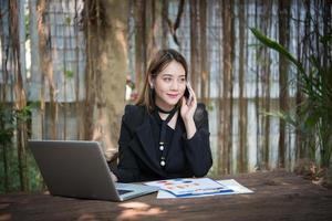 zaken vrouw praten over de telefoon en met behulp van haar laptop zittend op een tafel thuis foto