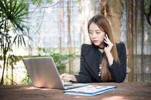 jonge zakenvrouw praten aan de telefoon zittend op haar werkplek foto