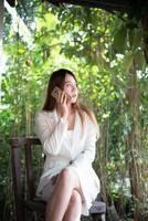 zakenvrouw praten op de mobiele telefoon en glimlachen zittend in eigen tuin foto