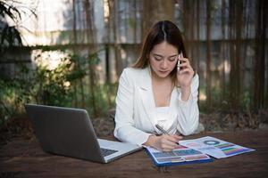 jonge zakenvrouw praten over de telefoon zittend op de werkplek foto