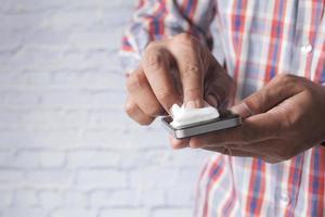 man schoonmaken van een mobiele telefoon display