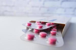 roze pillen in blisterverpakkingen in een doos op tafel