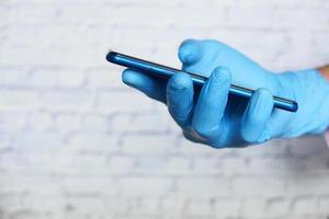 hand die handschoenen draagt die slimme telefoon bekijken