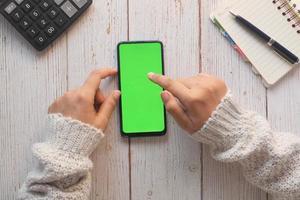bovenaanzicht van vrouw met behulp van mobiele telefoon met groen scherm