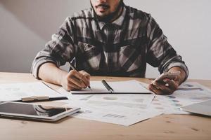 jonge zakenman schrijft in een notitieblok tijdens het analyseren van bedrijfsgegevens in kantoor foto