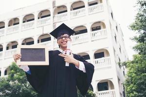 gelukkige afgestudeerde student met een schoolbord in de hand foto