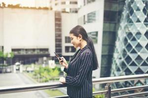 jonge Aziatische zaken vrouw met behulp van mobiele telefoon foto