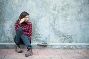 jonge hipster vrouw in coole outfit, zittend op de grond en praten aan de telefoon