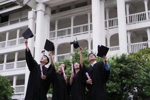 groep succesvolle studenten afstuderen hoeden in de lucht gooien en vieren foto