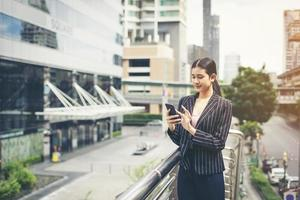 jonge Aziatische zakenvrouw met behulp van mobiele smartphone foto