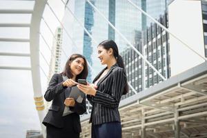 twee zakenvrouw met behulp van een smartphone en werk voor het kantoor bespreken foto