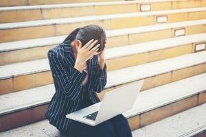 zakenvrouw met behulp van laptop zittend op trappen