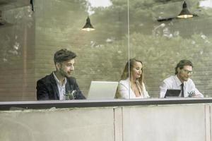 gelukkige collega's die op laptops samen in bureau werken foto
