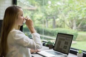 jonge zakenvrouw koffie drinken tijdens het werken op haar laptop op kantoor foto