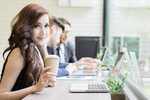 zakenvrouw koffie drinken kijken naar haar laptop terwijl collega's op de achtergrond communiceren foto