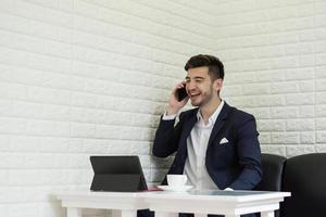 jonge zakenman met behulp van smartphone tijdens het werken op zijn laptop op kantoor foto