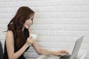 jonge zakenvrouw koffiekopje houden en laptop kijken foto