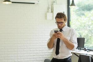 jonge zakenman met behulp van smartphone tijdens het werken op kantoor foto