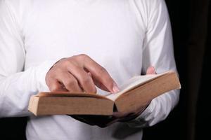 hand met een boek op zwarte achtergrond foto