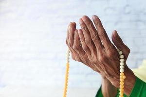 close-up van de hand van de senior vrouw bidden op ramadan foto