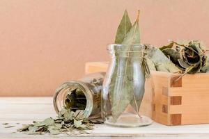 fles gedroogde laurierblaadjes en een houten kist foto