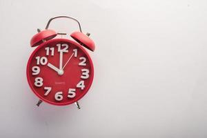 rode wekker geïsoleerd op een witte achtergrond foto