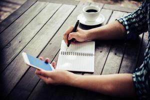close-up van zakenman met behulp van smartphone tijdens het werken in het café foto