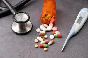 pillen en stethoscoop op zwarte achtergrond