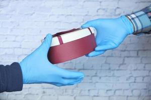 hand in handschoenen met een geschenk