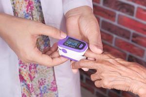 senior vrouw met behulp van een pulsoxymeter