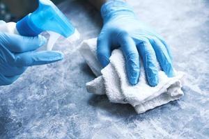 handen die een oppervlak desinfecteren