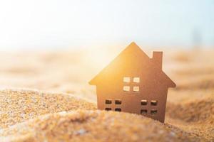 close-up van een klein huismodel in het zand met zonlichtachtergrond foto
