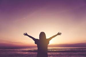 vrouw steekt handen omhoog naar de hemel foto