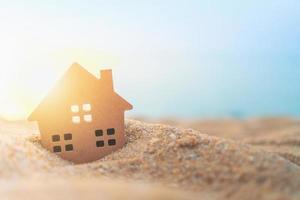 close-up van een klein huismodel in het zand met zonlichtachtergrond
