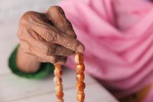 de hand van de oude vrouw met gebedskralen foto
