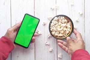 man met behulp van slimme telefoon en popcorn eten