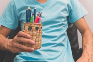 man met potloden en pennen