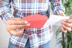 man die een rode envelop opent foto