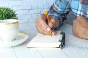 man schrijven op een notitieblok