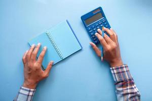 man met behulp van rekenmachine op blauwe achtergrond