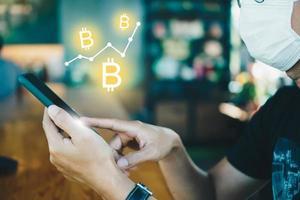 persoon die smartphone met bitcoin-pictogrammen gebruikt foto