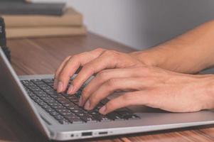 menselijke handen met behulp van computer om te werken en te communiceren foto