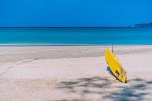 surfplank op zomerstrand met zonlicht en blauwe lucht foto
