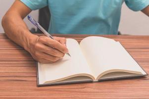 persoon die een boek schrijft aan een bureau foto